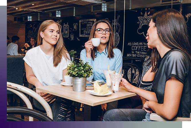 Three woman sitting at a cafe enjoying coffee and milkshakes